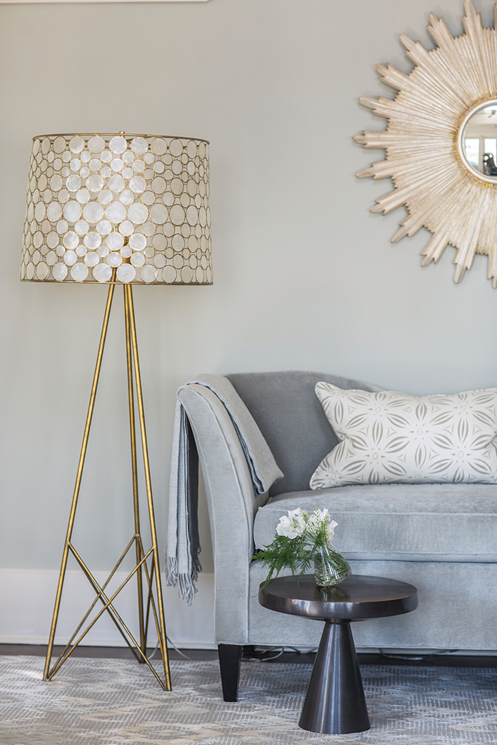 Brass accents create a chic lounge area in the master bedroom.